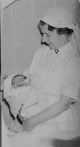 Jordmor Kristine Stang med nyfødt barn. Ukjent fotograf.