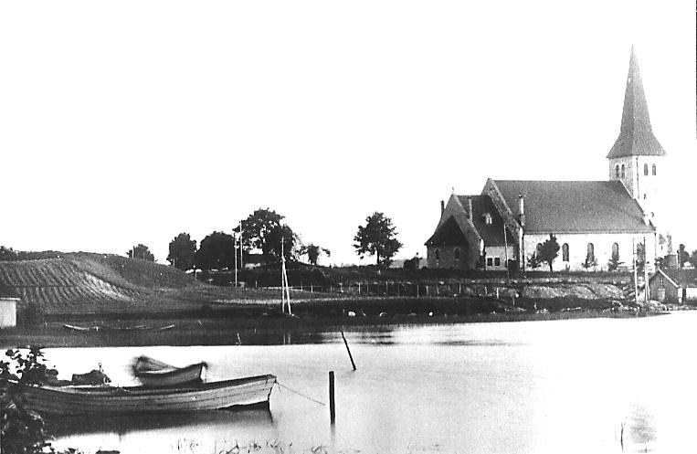 Tune kirke i 1920. Tunevannet i forgrunnen med Klokkerød til venstre. Foto: Sarpsborg kommunes fotoarkiv